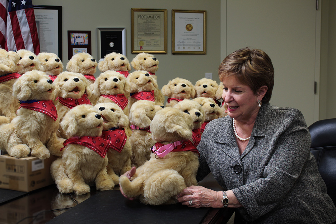 Alzheimer's Community Care President and CEO Mary M Barnes sitting with JOY FOR ALL Companion Pets used as Therapeutic Robotic Pets