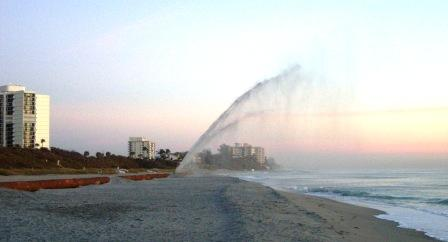 beach renourishmnet equipment spraying sand on beach